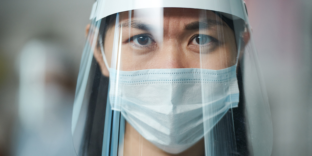 Young serious nurse in uniform and protective workwear looking at you through transparent mask